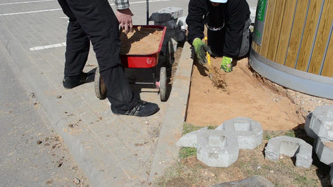 workers take sand from a small red wheelbarrow strew the ground Footage
