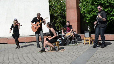 rock band with woman vocalist play music and sing near church Footage
