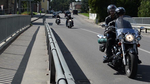 bikers ride motorcycle people pass bridge road Footage