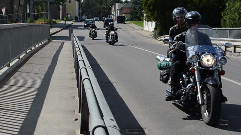 bikers ride motorcycle people pass bridge road Footage