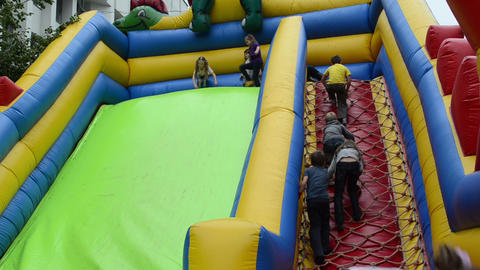 children climb and slide on inflatable rubber castle playground Footage