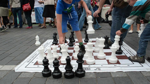 kids play chess game in city street event with huge figures Footage