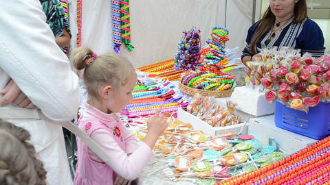 parents buy colorful sweet candy for kids in city street fair Footage