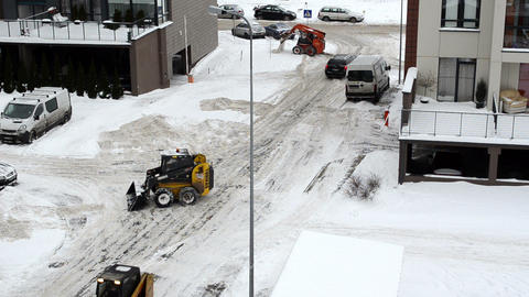 small tractors clean snow street near flat houses parking lot Footage