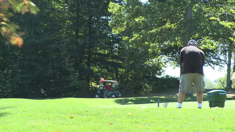 Golfer swings with driver to hit ball off tee (2 of 2) Footage
