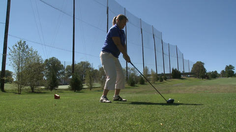 Female golfer drives ball off tee Stock Video Footage