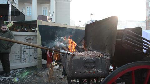 man bake meat chop firewood spring street fair fire smoke rise Footage