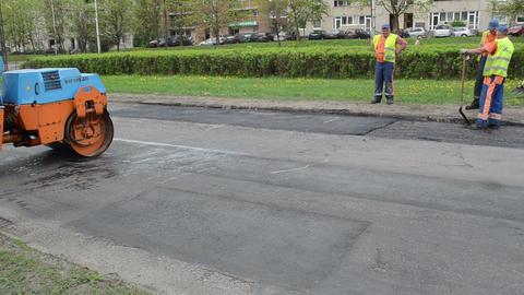 people work heavy asphalt road repair roller passing cars... Stock Video Footage