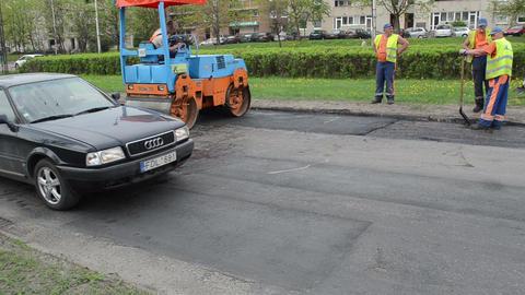 people work heavy asphalt road repair roller passing cars street Footage