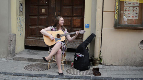 Young honest vocalist woman sing play guitar in old town... Stock Video Footage
