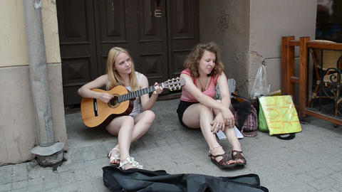 nice girls students sit old town street play with guitar... Stock Video Footage