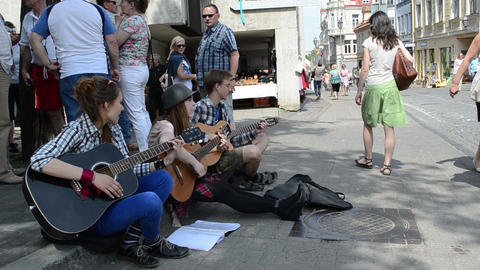 teenagers play guitar and sing sit on street pavement Stock Video Footage