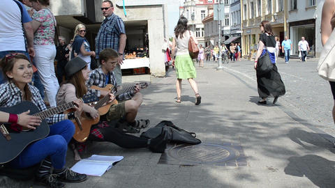 teenagers play guitar and sing sit on street pavement Footage