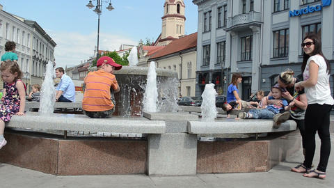 People with children have fun near city fountain hot sunny day Footage