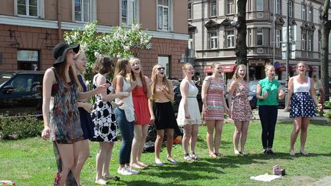 chorus girls sing glee song in public street festival Stock Video Footage