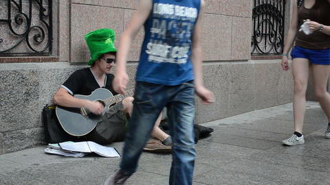 honest singer with green hat play guitar and sing on street Footage