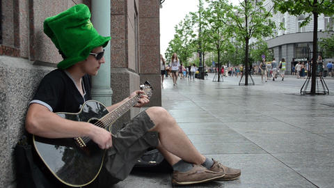 simple man singer with green hat play guitar and sing on street Footage