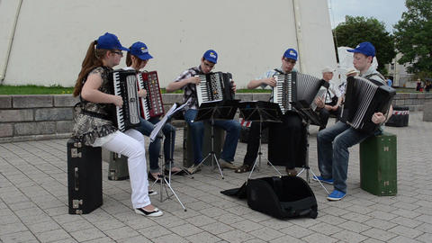Group of young musicians play perform accordion music in street Footage
