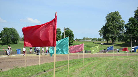 Various color flags fly wave and blur people walk in background Footage