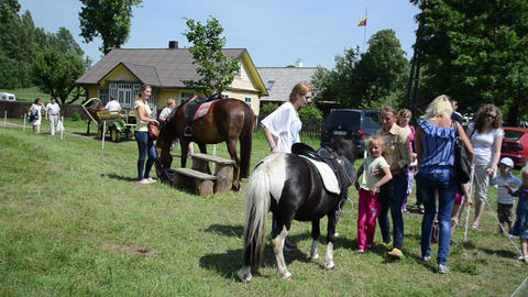 Parents ride their kids on pony and horse for money in festival Footage