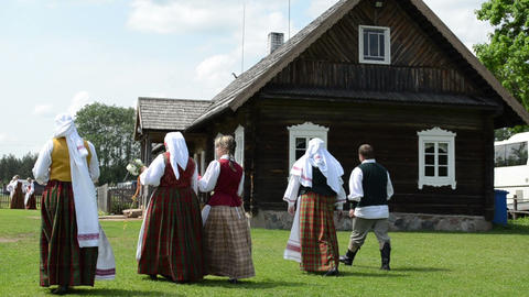 women and men in traditional clothes walk near rural... Stock Video Footage