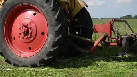 tractor sharp blade cuts grass farmer field Live Action