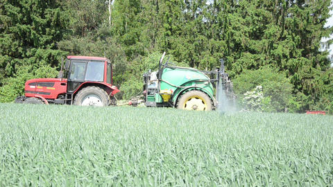 farmer driving tractor fertilizer spray nozzles along forest Footage