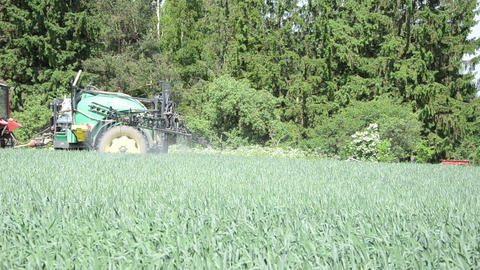 farmer driving tractor fertilizer spray nozzles along forest Stock Video Footage