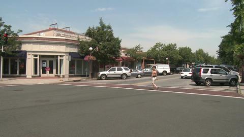 Person walking across intersection on crosswalk Stock Video Footage