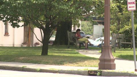 Woman sitting on bench along sidewalk Stock Video Footage