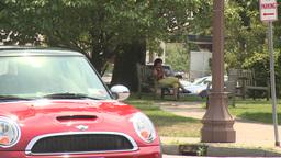 Woman sitting on bench along sidewalk Footage