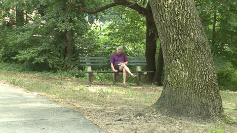 Man sitting on bench in park Footage
