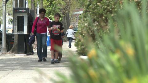 People walking along sidewalk with plants on the side (2... Stock Video Footage