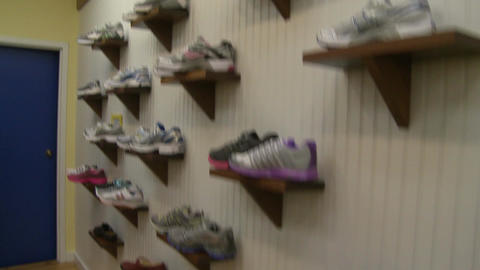 Athletic shoes displayed on shelves on a wall Footage