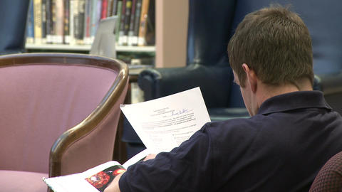 Man reading papers in a library Footage