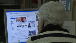 Elderly woman using the computer in the library Live Action