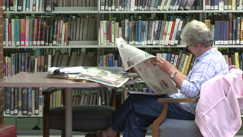 Mature woman reading a newspaper in the library (2 of 2) Stock Video Footage