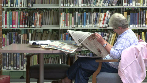 Mature woman reading a newspaper in the library (2 of 2) Footage