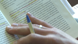 Person using a pen to follow the line he is reading in a book (2 of 2) Live Action