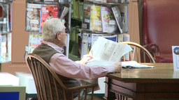 Elderly man reading a newspaper in the library Live Action