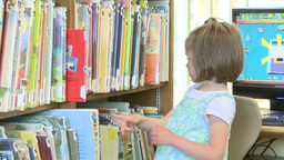 Young child getting a book from shelf at the library (2 of 3) Live Action