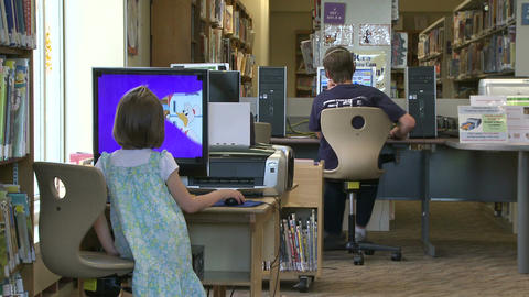 Two children using the computers at the library Footage