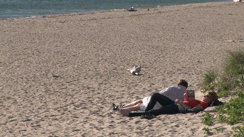 A couple lying on the sand reading Live Action