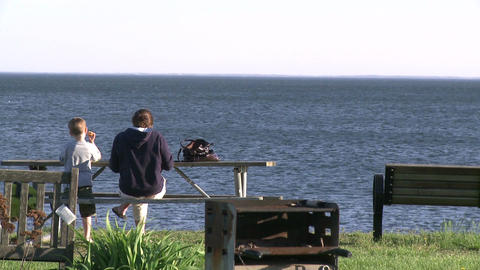 Mother and son sitting at a picnic table overlooking the ocean (1 of 2) Footage