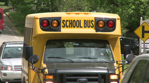 Small school bus traveling on road (2 of 5) Live Action
