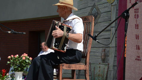 old man with straw hat from the sun plays with small accordion Footage