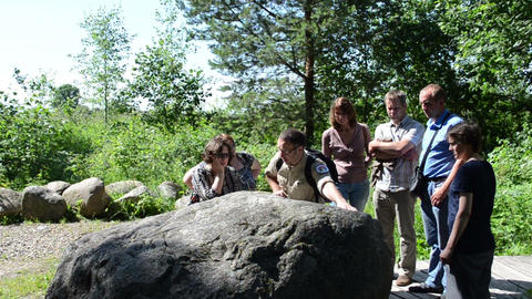 tourist people and guide tell history story about old big stone Live Action