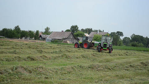 Heavy agricultural machines prepare hay animal fodder in field Footage