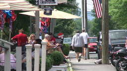 Man walking down sidewalk by a sidewalk cafe Footage