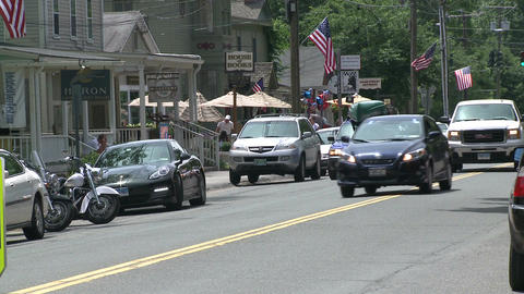 Cars and a motorcycle parked along the stores down town Footage